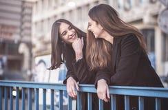 Городские девушки наслаждаясь днем вне в городе Стоковые Изображения