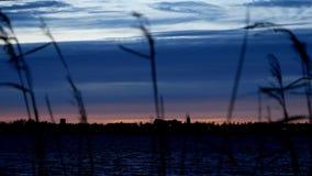 Городское Bemidji увиденный приходить в фокус через озеро Ирвинга, первое озеро на реке Миссисипи после захода солнца акции видеоматериалы