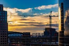 Городской восход солнца над строительной площадкой стоковое изображение