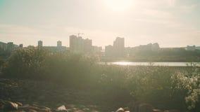 Городской ландшафт с озером на заходе солнца отраженном в озере Городской пейзаж на предпосылке озера на заходе солнца сток-видео