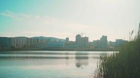 Городской ландшафт с озером на заходе солнца отраженном в озере Городской пейзаж на предпосылке озера на заходе солнца видеоматериал