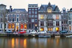 Городской пейзаж - взгляд вечера домов с праздничными украшениями и канал с шлюпками, город города Амстердама стоковая фотография
