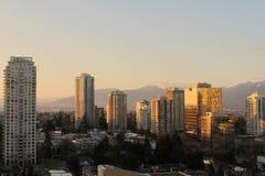 Городской пейзаж и горы на заходе солнца стоковое изображение rf