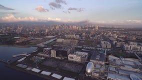 Городской пейзаж Манилы, Филиппин Близко к Bay City, Pasay с светом и зоной предпринемательства захода солнца Близко к молу Азии видеоматериал