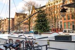 Городской пейзаж рождества - взгляд плавучего дома с рождественской елкой в старом районе Амстердама стоковые изображения rf
