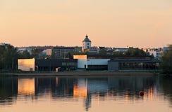 Городской пейзаж спокойного озера поверхностный отражая в комплекте солнца Стоковая Фотография
