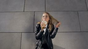 Городской портрет молодой привлекательной блондинкы женской в белом milkshake футболки и куртки выпивая через солому внутри сток-видео