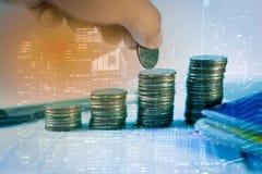 Город и рука двойной экспозиции кладя дело стога монетки денег растя чеканит сбережениа кучи дег рук принципиальной схемы защищая стоковое изображение