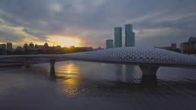 город над заходом солнца Туристы идут вдоль столба над рекой astana видеоматериал
