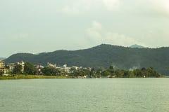 Город на озере на предпосылке зеленых гор стоковые фотографии rf