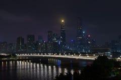 Город ночи современный с небоскребами Мост над рекой, здания города накаляет вечером Небо в облаках прячет здание стоковое фото rf