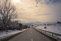 город около железнодорожной дороги светит солнцу снежка к древесине зимы Проселочная дорога через концепцию перемещения леса Стоковые Изображения RF