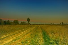 Город lena травы желтого цвета страны дороги лета вечера в distan Стоковая Фотография