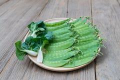 Горохи и Пак choi на деревянном блюде стоковая фотография