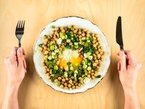 Горохи цыпленока с яичницами, луком и руками стоковые фотографии rf