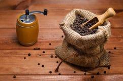 Горохи черного перца в мельнице мешка и перца на деревянном столе Стоковые Изображения RF
