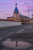 Городок на заходе солнца с отражением в лужице Стоковые Фото