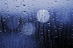 Городская жизнь ночи через windscreen: темнота и дождь Стоковое Фото