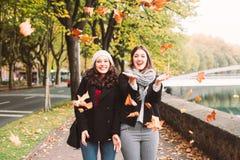 Городские смешные девушки наслаждаясь осенью Стоковая Фотография
