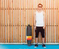 Городские солнечные очки и скейтборд человека представляя на деревянной предпосылке планок Хороший смотреть холодная ванта Нося б Стоковые Фото