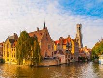 Городской пейзаж Брюгге, Фландрии, Бельгии Намочите канал на Rozenhoedkaai с старыми кирпичными зданиями и башней колокольни даль Стоковые Изображения RF