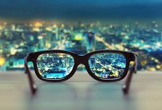Городской пейзаж ночи сфокусированный в объективах стекел