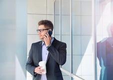 Городской привлекательный бизнесмен с прибором и кофе телефона дальше  Стоковые Изображения