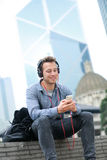Городской человек на наушниках умного телефона нося Стоковое Изображение RF