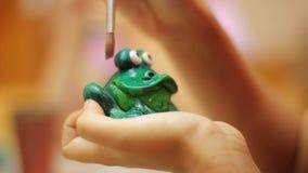 Горшечник на работе Руки крупного плана женские крася зеленую керамическую лягушку сток-видео