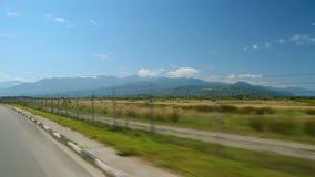 Горы Кавказа на горизонте увиденном от автоматического управляя шоссе, перемещении автомобилем видеоматериал