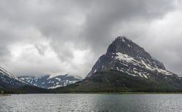 Горы покрытые снегом и ясное озеро Стоковые Фото