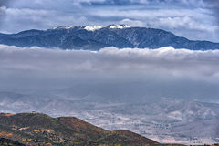 Горы покрытые снегом с грядой облаков Стоковые Фотографии RF