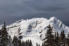 Горы покрытые с снегом и окруженные облаками Стоковое фото RF