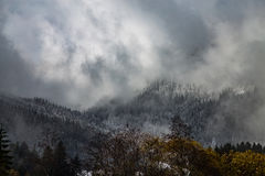 Горы покрытые с снегом и окруженные облаками Стоковое Изображение