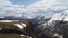 Горы предусматриванные в снеге против неба с облаками сток-видео