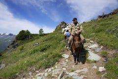 ГОРЫ ALTAI, РОССИЯ - 14-ОЕ ИЮЛЯ 2016: Местные люди используя лошадей для транспорта на горе Belukha Стоковое Изображение RF