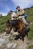ГОРЫ ALTAI, РОССИЯ - 14-ОЕ ИЮЛЯ 2016: Местные люди используя лошадей для транспорта на горе Belukha Стоковая Фотография