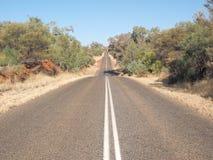 Горячая дорога битума к горизонту на приводе Larapinta стоковая фотография
