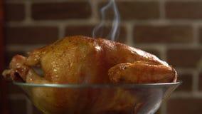 Горячая жареная курица в стеклянном шаре поворачивает дальше предпосылку красной кирпичной стены сток-видео