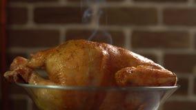 Горячая жареная курица в стеклянном шаре против красной кирпичной стены видеоматериал