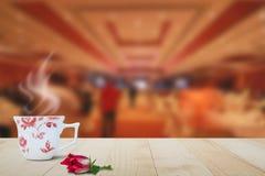Горячая кофейная чашка и красный цветок на верхней части деревянного стола на запачканной предпосылке лобби гостиницы Стоковая Фотография