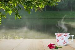 Горячая кофейная чашка и красный цветок на верхней части деревянного стола на запачканной туманной предпосылке озера и леса Стоковое Изображение RF