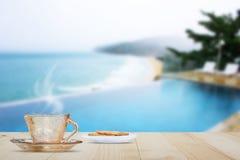 Горячая кофейная чашка на верхней части деревянного стола на запачканной предпосылке бассейна и пляжа Стоковая Фотография