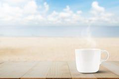 Горячая кофейная чашка на верхней части деревянного стола на запачканном backg пляжа Стоковое Изображение