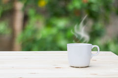 Горячая кофейная чашка на верхней части деревянного стола на запачканной предпосылке сада Стоковые Фотографии RF