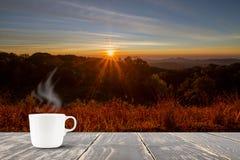 Горячая кофейная чашка на верхней части деревянного стола на запачканном луге и гора с солнечным светом с пирофакелом во время во Стоковые Изображения