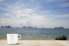Горячая кофейная чашка на верхней части деревянного стола на запачканной предпосылке пляжа Стоковые Фотографии RF
