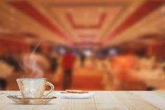 Горячая кофейная чашка на винтажной верхней части деревянного стола на предпосылке лобби гостиницы Стоковое Изображение