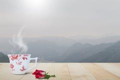 Горячая кофейная чашка с паром и красным цветком на винтажной верхней части деревянного стола на запачканной туманной предпосылке Стоковая Фотография