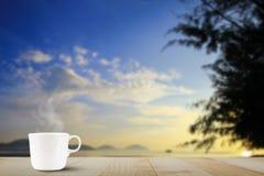 Горячая кофейная чашка с паром на верхней части деревянного стола на запачканных голубом небе и пляже во время восхода солнца Стоковая Фотография